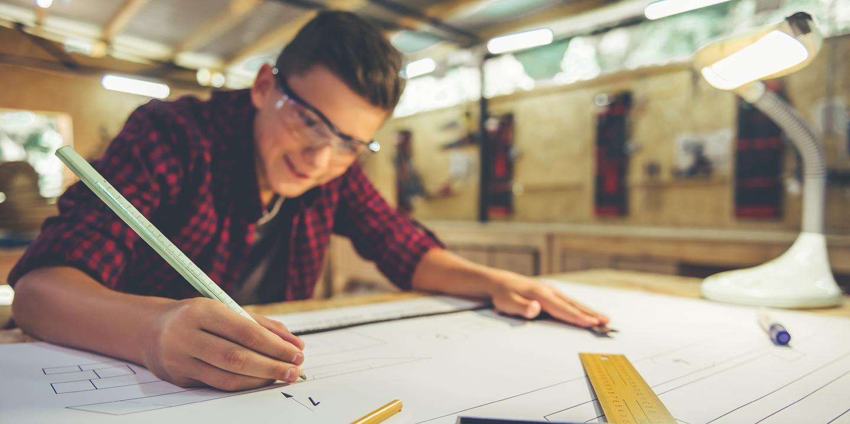 Junge zeichnet einen Plan