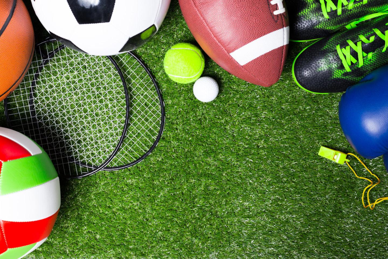 Eine Wiese auf der ein Volleyball, ein Basketball,, Badmintonschläger, ein Fußball, ein Tennisball, ein Golfball, ein Football, Fußballschuhe, ein Boxhandschuhe und eine Trillerpfeiffe liegen