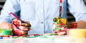 Jugendlicher mit farbigen Händen beim Malen