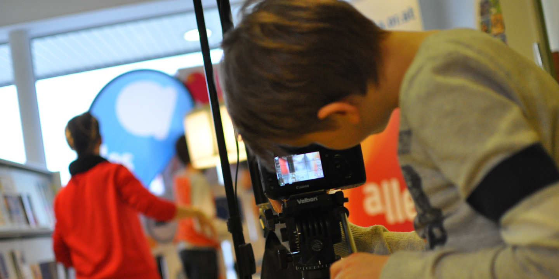 Jugendlicher blickt durch eine Kamera und filmt.