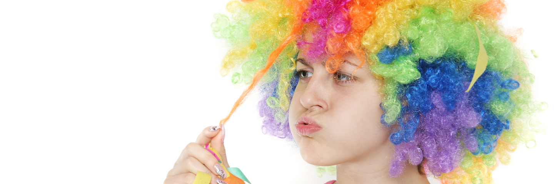 Mädchen mit bunter Perücke zieht an einer Strähne