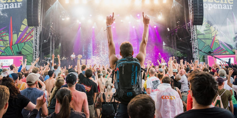 Besucher vor einer Bühne bei einem Openair-Konzert