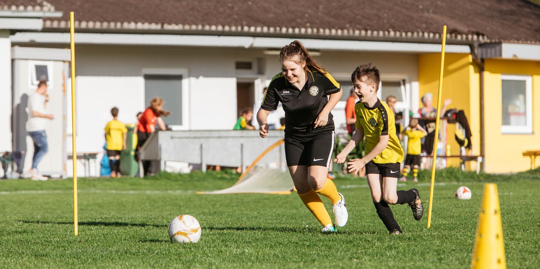 Jugendliche beim Fußballspielen mit einem Buben.