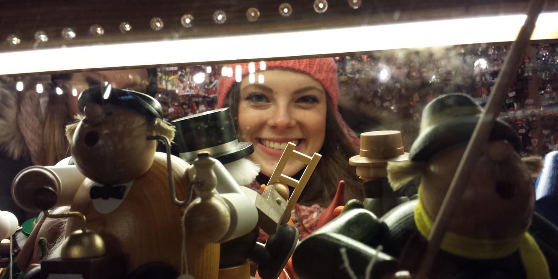 Ein Mädchen schaut ins Schaufenster eines Weihnachtsmarktstandes.