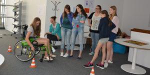Jugendliche versuchen mit einem Rollstuhl einen Parcours zu fahren, um so die Herausforderungen von RollstuhlfahrerInnen zu erleben.