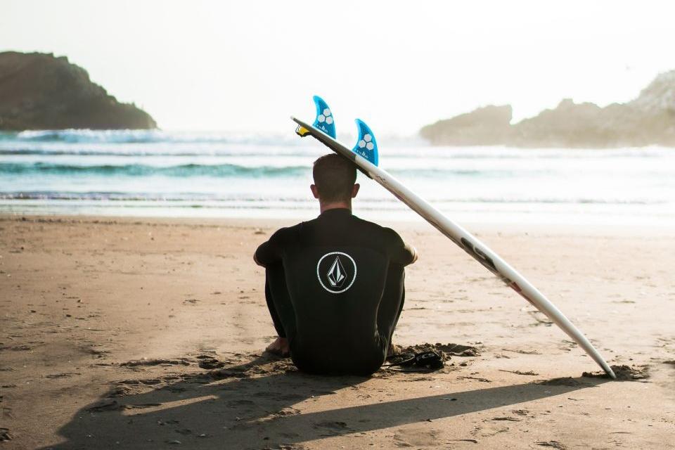 Mann sitzt am Strand mit Surfbrett und schaut aufs Meer