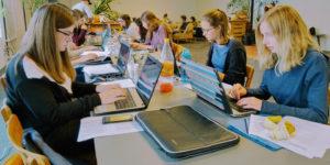 Jugendliche, die vor Laptops sitzen und schreiben.