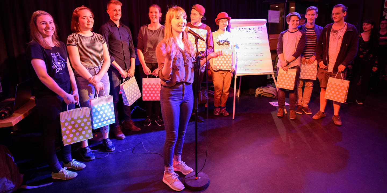 Poetry Slammerin bei ihrer Performance hinter einem Mikrophon