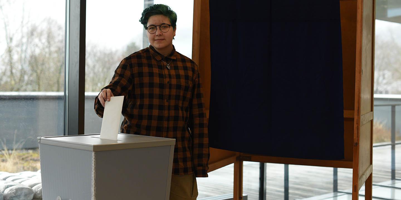 Jugendliche wirft ihr Wahlkuvert in eine Wahlurne.