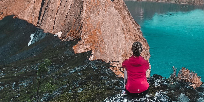 Eine junge Frau sitzt in den Bergen in Norwegen und betrachtet einen See und die Berge.