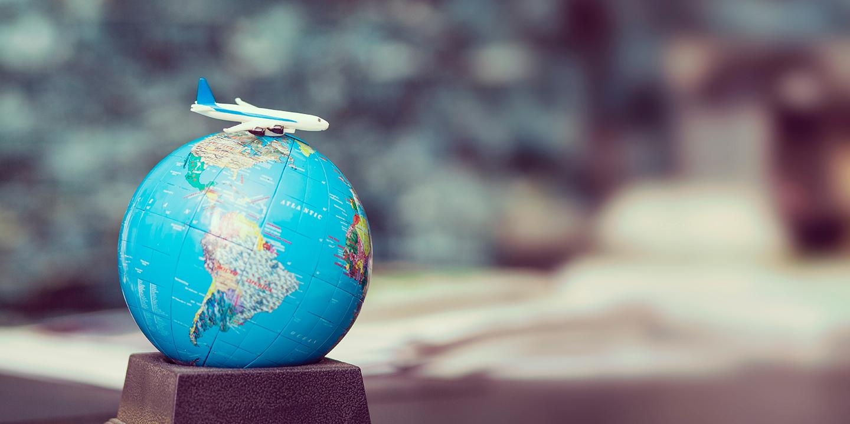 Globus mit einem Spielzeugflugzeug drauf.