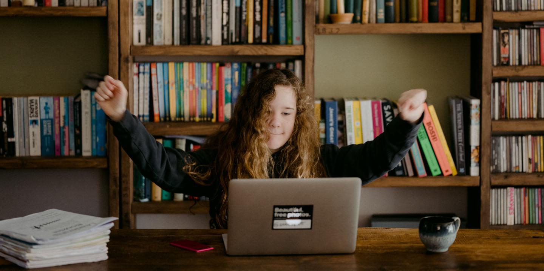 Juendliche vor einem Laptop, die vor Freude die Hände nach oben reißt.
