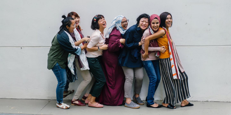 Eine Gruppe von Frauen, die lachend in einer Reihe stehen und sich halten.