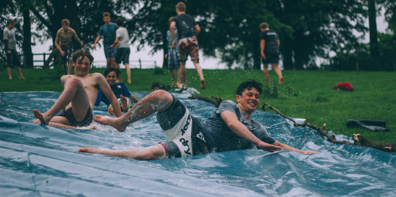 Junge Burschen runtschen eine Wasserplane runter.