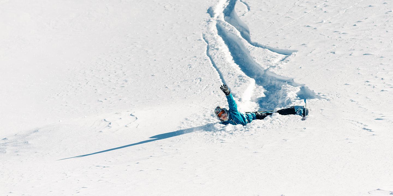 Ein Mädchen liegt nach einem Sturz mit ihren Ski im Schnee und winkt.