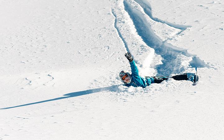 Mädchen liegt nach einem Sturz mit seinen Ski im Schnee und winkt